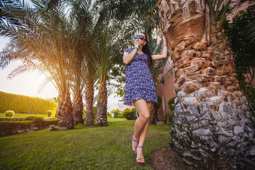 woman is walking in the garden with palm trees