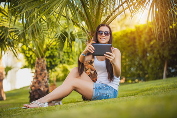 girl with tablet in the palm garden