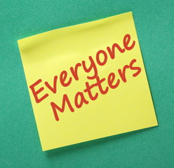 The phrase Everyone Matters written on a yellow sticky note