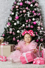 Little girl near the Christmas tree with gifts