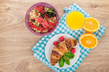 Healthy breakfast with muesli, berries, orange juice and croissa