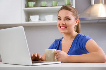 Cute young girl typing on laptop and drinking coffee