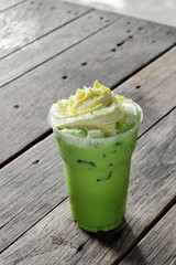 close up cold green tea and cream in plastic glass