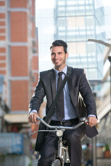 Smiling businessman riding a bicycle