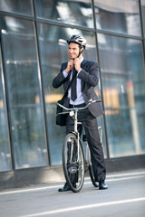 Businessman puts the bicycle helmet on head