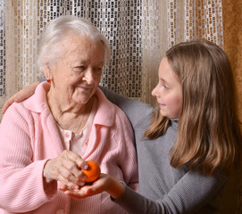 Girl giving mandarin oranges to his grandmother