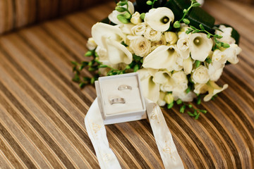 Wedding rings with calla and roses bouquet