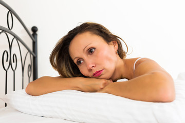 Sad female lies  in bed