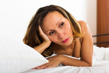 Thoughtful woman lies  in bedroom
