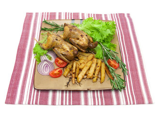 dish with fried woodcock and vegetables on a napkin on white bac