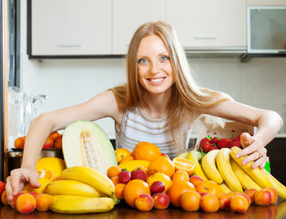 Positive  woman with heap of  fruits