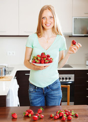 Happy blonde girl holding  heap of strawberries