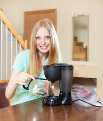 Young blond with new electric coffee maker at home