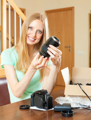 Happy woman unpacking new objective for camera at home