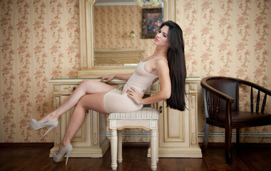 Charming young brunette woman in tight fit short nude dress