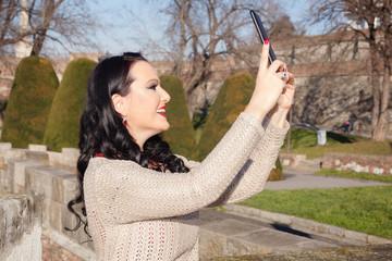 Woman taking self-portrait outdoors