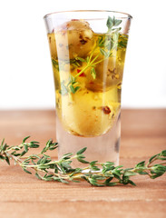 Green olives in oil with spices and rosemary in glass