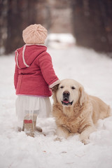 Little girl with dog at winter park