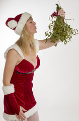 Woman blows kiss in Santa outfit with bunch of Mistletoe