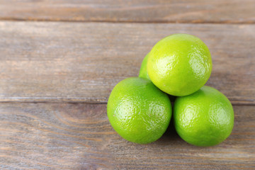 Fresh juicy limes on wooden background