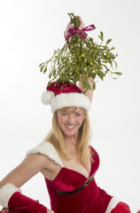 Woman in Santa outfit with bunch of Mistletoe at Christmas
