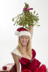 Woman in Santa outfit holding bunch of Mistletoe