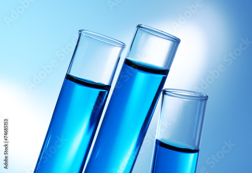 canvas print picture Inclined test-tubes with blue water on the shadows background