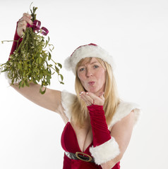 Woman blows kisses in Santa outfit with bunch of Mistletoe