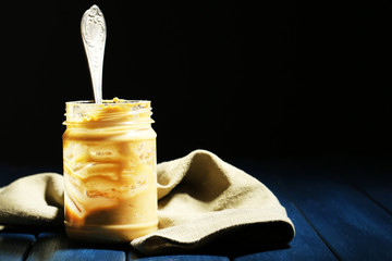 Empty peanut butter jar on table, on dark background