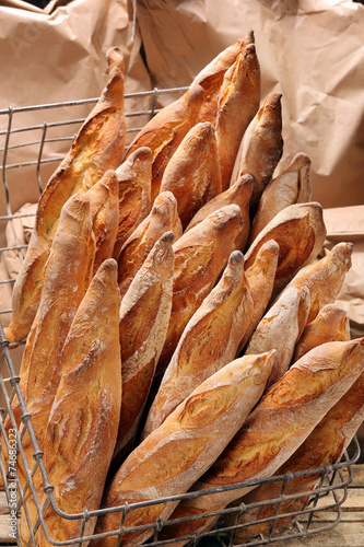 Papiers peints Pain French baguettes in metal basket in bakery