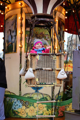 Cheerful toddler girl enjoying merry-go-round
