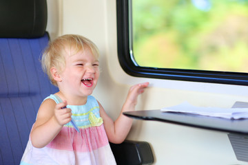 Happy little girl enjoying trip by train