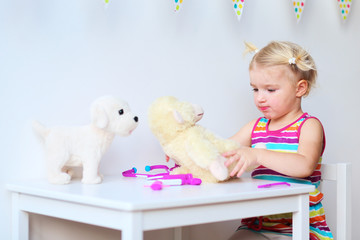 Little girl playing doctor role game with her toys