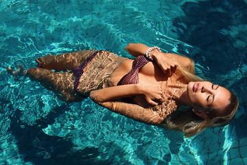 sexy woman with blond hair in bikini relaxing in swimming pool