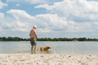 Senior man with dog in water