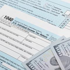 USA Tax 1040 Form 1040 and 100 US dollar bills