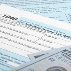 USA 1040 Tax Form with 100 US dollar bills