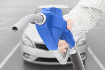 Blue color fuel pump gun in hand with car on background