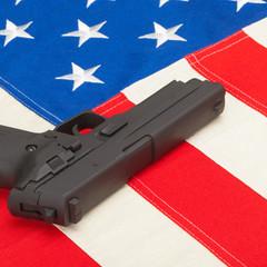 Handgun laying over USA flag - self-defense law concept