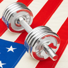 Metal dumbbells over US flag - healthy lifestyle concept