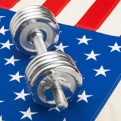 Metal dumbbell over US flag - healthy lifestyle concept