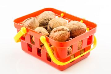 walnuts in red basket on white backround