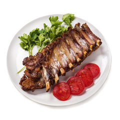 Baked pork ribs with vegetables isolated on white background