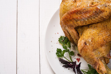 Baked chicken with spices on a light wooden table and place for