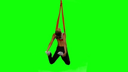 Young woman making antigravity yoga exercises with red hammock
