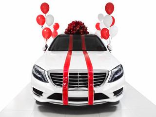 New year gift car. White luxury sedan with ballons