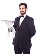 Portrait of handsome waiter holding an empty tray over white bac