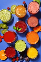 Glasses of tasty fresh juice, on blue background