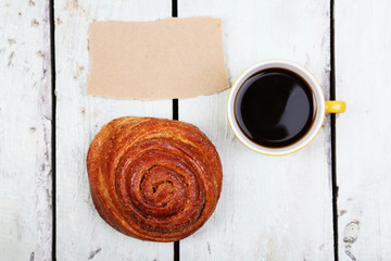 Composition of coffee, fresh bun and paper card