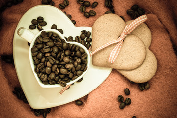 Coffee beans in heart shaped cup and dessert